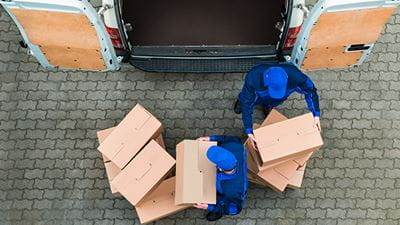 Delivery men unloading cardboard boxes