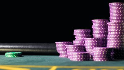 Stacks of purple gambling chips by three green chips on gaming table